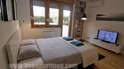 Krevet i izlaz na terasu BAŠTA apartman u Blok A